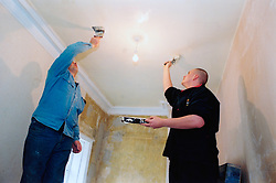 Young men renovating a house on New Deal government training scheme for unemployed people; Bradford Yorkshire UK