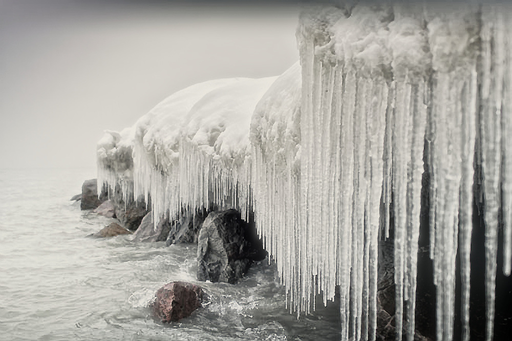 A row of icicles hang off the edge of a snow covered rock-bed at Toronto waterfront (Canada).