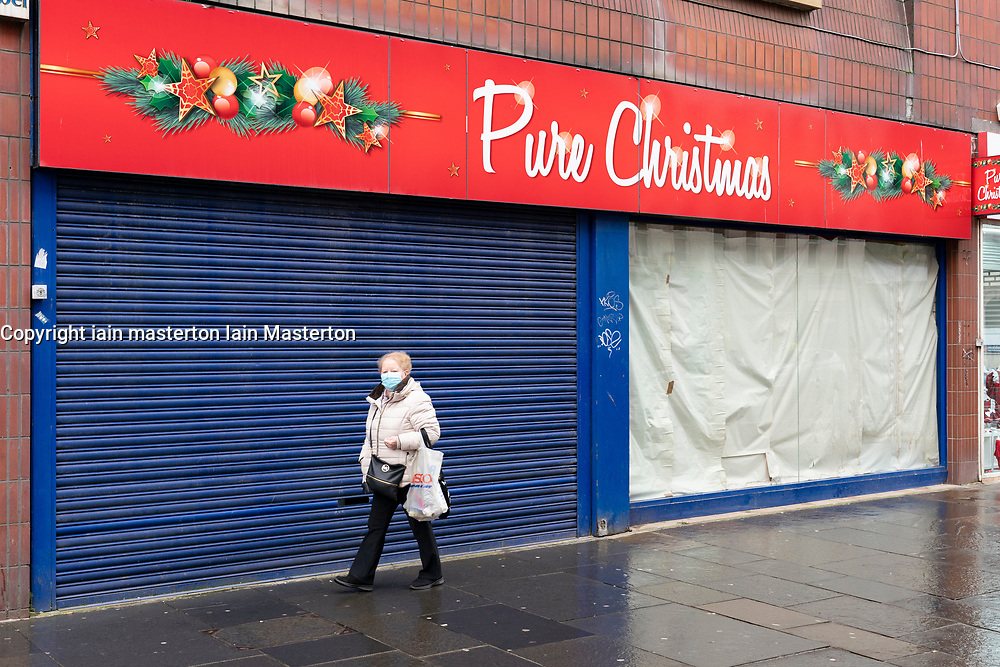 Glasgow, Scotland, UK.1 December 2020. Coronavirus health warnings, shop display and graffiti in Glasgow city centre. Pictured; Woman walks past a closed and shuttered speciality Christmas shop.  Iain Masterton/Alamy Live News
