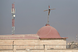 Licensed to London News Pictures. 23/10/2016. A wooden cross erected by Iraqi Army Counter Terrorism troops and draped with the Iraqi flag is seen on a roof of the Mart Shmony Church in Bartella, Iraq.<br /> <br /> Bartella, a mainly Christian town with a population of around 30,000 people before being taken by the Islamic State in August 2014, was captured two days ago by the Iraqi Army's Counter Terrorism force as part of the ongoing offensive to retake Mosul. Although ISIS militants were pushed back a large amount of improvised explosive devices are still being found in the town's buildings. Photo credit: Matt Cetti-Roberts/LNP