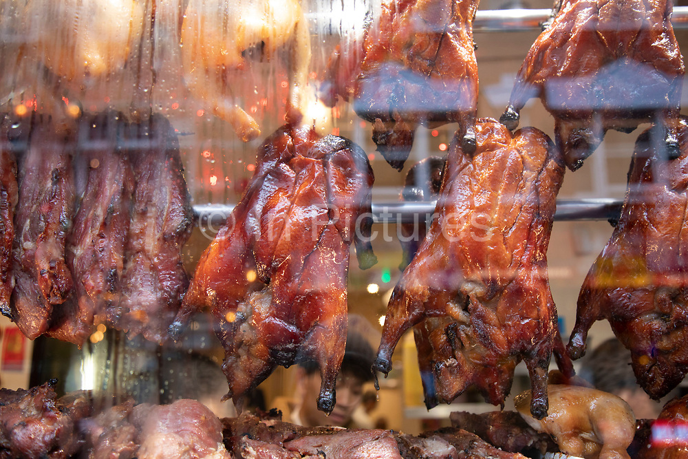 Chinese restaurant window with crispy Peking Ducks hanging in the window in Chinatown on 27th January 2020 in London, United Kingdom. These ducks have been covered in spices and deep fried to give them a glistening and crispy skin, a speciality of Chinese cooking. The present Chinatown is in the Soho area occupying the area in and around Gerrard Street. It contains a number of Chinese restaurants, bakeries, supermarkets, souvenir shops, and other Chinese-run businesses and is in itself a major tourist destination.