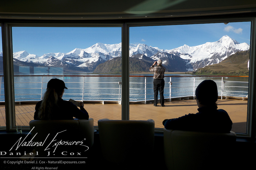 Guests onboard the Seabourn Quest enjoy the view of the mountinas surrounding King Edward Cove, on a beautiful, sunny morning in Grytviken, South Georgia.