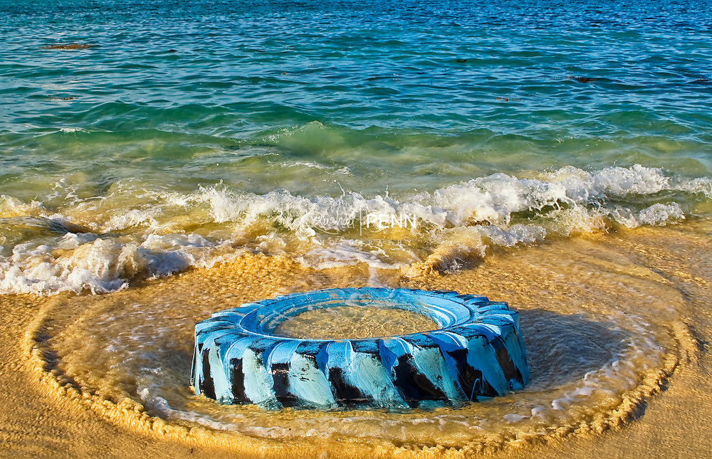 An old blue painted tire left on the shore of Sandy Port Beach as the waves beat upon it, Nassau the Bahamas The Bahamas Seascape, fine art photography in the Bahamas. Waves water, beaches and sunsets