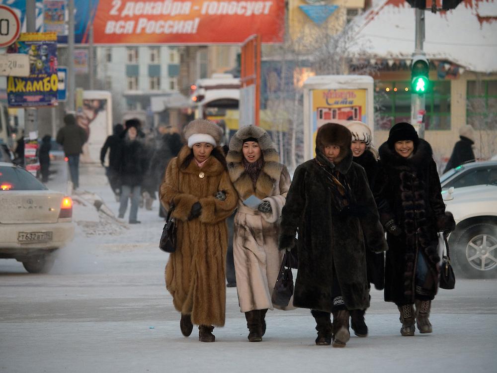 Passantinnen in der Innenstadt von Jakutsk. Jakutsk wurde 1632 gegruendet und feierte 2007 sein 375 jaehriges Bestehen. Jakutsk ist im Winter eine der kaeltesten Grossstaedte weltweit mit durchschnittlichen Winter Temperaturen von -40.9 Grad Celsius. Die Stadt ist nicht weit entfernt von Oimjakon, dem Kaeltepol der bewohnten Gebiete der Erde.<br /> <br /> Passersby in the city center of Yakutsk. Yakutsk was founded in 1632 and celebrated 2007 the 375th anniversary - billboard announcing the celebration. Yakutsk is a city in the Russian Far East, located about 4 degrees (450 km) below the Arctic Circle. It is the capital of the Sakha (Yakutia) Republic (formerly the Yakut Autonomous Soviet Socialist Republic), Russia and a major port on the Lena River. Yakutsk is one of the coldest cities on earth, with winter temperatures averaging -40.9 degrees Celsius.