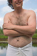 man standing bare breasted with towel around his waist