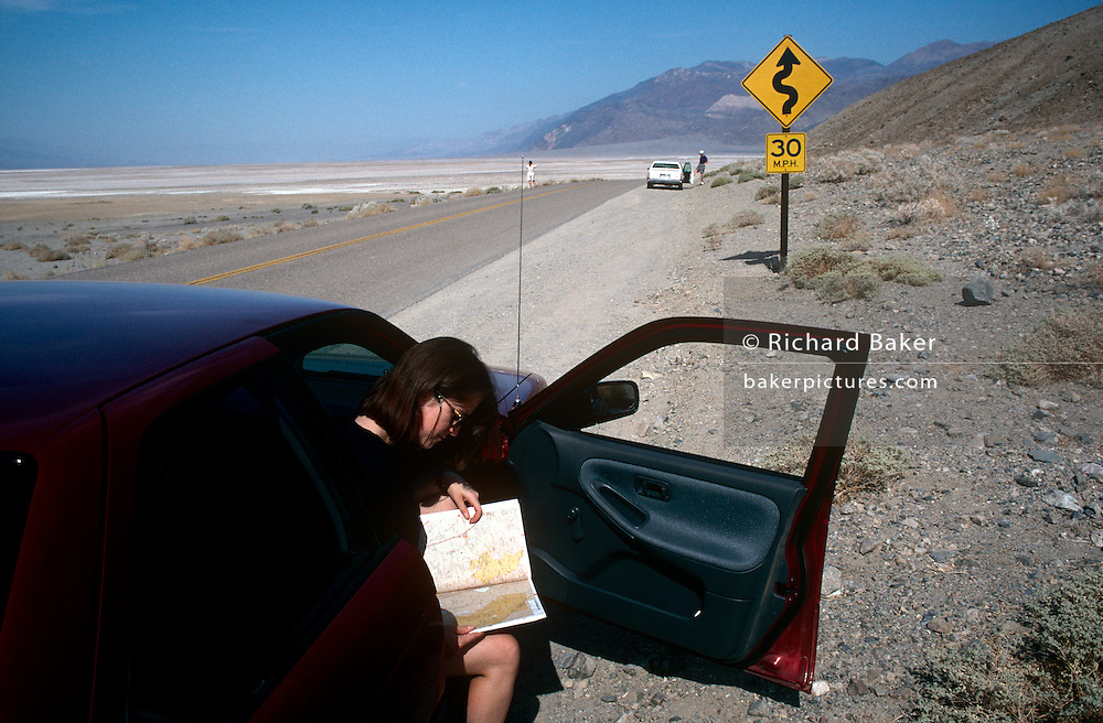 A woman toutist reads a map of the area, stopped by the side of highway 190 in Death Valley, California. A road sign warns of the bending road that skirts the arid area, dangerous for those caught without transport and water. Death Valley is a desert valley located in Eastern California. Situated within the Mojave Desert, it is the lowest and driest area in North America. Death Valley has the record highest recorded air temperature in the world. The valley received its English name in 1849 during the California Gold Rush and called Death Valley by prospectors.