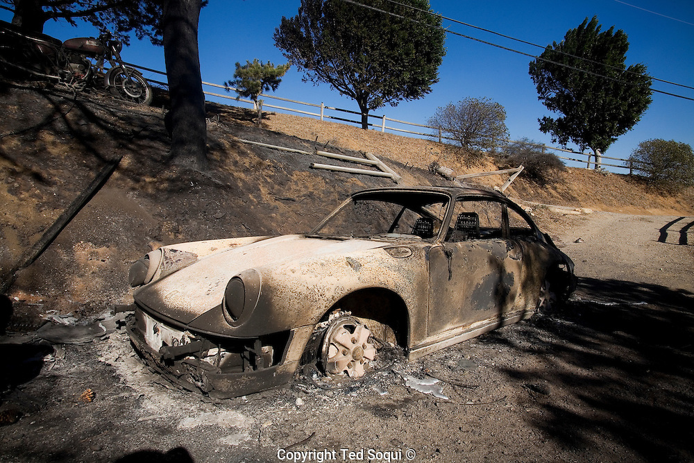 Malibu resident Carol Stoddard looks over her prized Porche that was destroyed by wild fire.. Her 7 level home was completely destroyed by wild fire. She escaped with her animals and a few pocessions..A Santa Ana wind driven wild fire that started near the top of Corral Canyon in Malibu, CA destroyed about 30 luxury homes worth around 50 million dollars. The fire was started by human activity according to authorities. Over 20,000 Malibu area residents were evacuated. Gov. Arnold Schwarzenegger continued the state of emergency he declared in last month's fire storm.