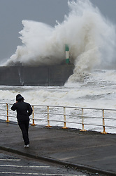 """© London News Pictures. 08/02/2014. Aberystwyth, UK. <br /> A woman walking in Gale force winds as giant waves strike the lighthouse at Aberystwyth, Wales at high tide. The winds are forecast to strengthen throughout the day, gusting up to 70 or 80 mph, and with the rising tide, their impact could be potentially damaging again. An amber """"be prepared"""" warning  has been issued by the Met Office for wind,. Photo credit: Keith Morris/LNP"""