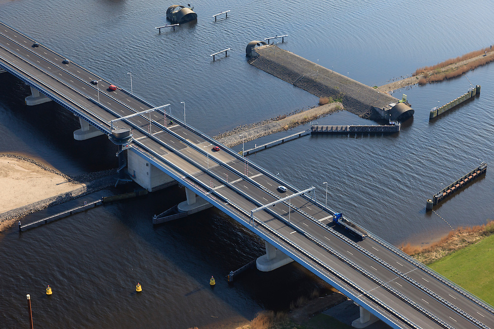 Nederland, Flevoland-Overijssel, Ramspol, 01-05-2013; nieuwe Ramspolbrug in de N50 met naast de brug het begin de balgstuw. De vaargeul het Ramsdiep met de strekdam.<br /> Ramspol, inflatable dike, between Ketelmeer and Black Water. The Balgstuw (bellow barrier) is a storm barrier and consists of an inflatable dam or dyke, composed of three bellows. Usually, each bellow rests on the bottom of the water, but now the bellows are inflated  because of maintenance.<br /> luchtfoto (toeslag op standard tarieven)<br /> aerial photo (additional fee required)<br /> copyright foto/photo Siebe Swart