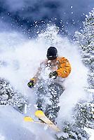 A skier bursts through snow covered trees at Jackson Hole Mountain Resort, Jackson Hole, Wyoming.