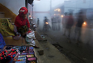 A Red Dao woman is barely awake as locals and tourists pass by her goods for sale in Sapa, the mountain town north of Hanoi and near the Chinese border. The city, near the highest point in Vietnam, is often shrouded in clouds, fog and rain. Robert Dodge, a Washington DC photographer and writer, has been working on his Vietnam 40 Years Later project since 2005. The project has taken him throughout Vietnam, including Hanoi, Ho Chi Minh City (Saigon), Nha Trang, Mue Nie, Phan Thiet, the Mekong, Sapa, Ninh Binh and the Perfume Pagoda. His images capture scenes and people from women in conical hats planting rice along the Red River in the north to men and women working in the floating markets on the Mekong River and its tributaries. Robert's project also captures the traditions of ancient Asia in the rural markets, Buddhist Monasteries and the celebrations around Tet, the Lunar New Year. Also to be found are images of the emerging modern Vietnam, such as young people eating and drinking and embracing the fashions and music of the west. His book. Vietnam 40 Years Later, was published March 2014 by Damiani Editore of Italy.