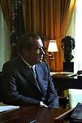 Richard Milhous Nixon (1913-1994) 37th President of the United States 1969-1974. Half-profile portrait seated at desk.