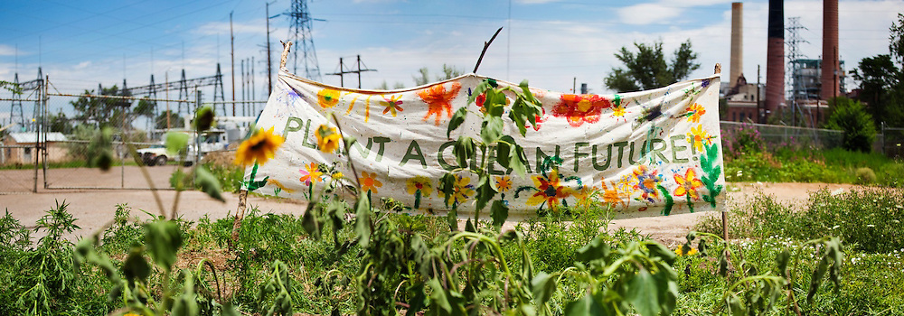 """The painted sign """"Plant a clean future"""" besides a garden planted in front of the coal-fired Valmont Power Plant in Boulder, Colorado to protest its continued operation."""