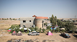 © Licensed to London News Pictures. 25/06/2014. Khanaqin, Iraq. Tents and cars used by Iraqi refugees, who also inhabit much of the unfinished house, are seen at a refugee camp on the outskirts of Bahari Taza village in Iraq. Located on the outskirts of Khanaqin, a town just 20 minutes from the front-line of the battle with ISIS insurgents, the Bahari Taza refugee camp, and its satellite camps, now house around 600 families from southern Iraq. Built by the local village leader to meet the influx of refugees from nearby Jalawla and Saidia, where intense fighting is still taking place. Turkman, Arab and Kurd, both Sunni and Shia, all live together in tents, barns and unfinished buildings waiting for the conflict to end. Photo credit: Matt Cetti-Roberts/LNP