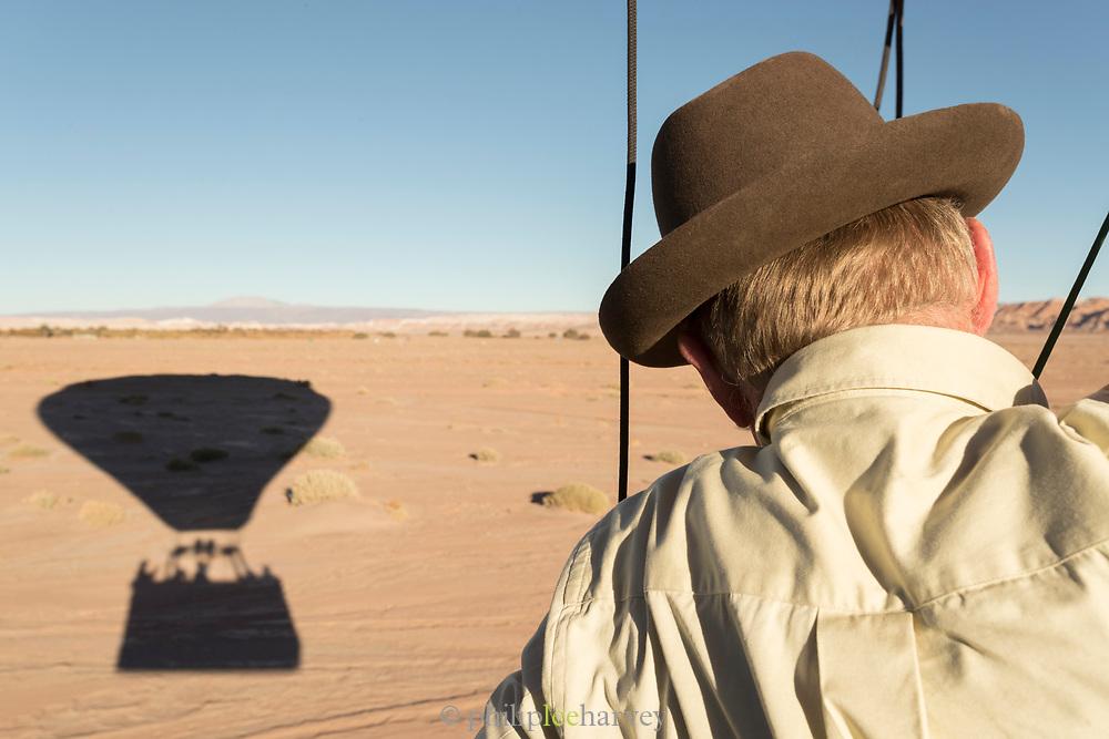 Rear view of man flying in hot air balloon and balloon shadow, Atacama Desert, Chile