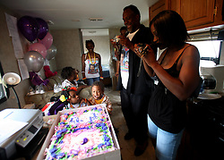29 August 2007. Lower 9th Ward, New Orleans, Louisiana. <br /> Second anniversary of Hurricane Katrina. Grand children Chyana Hurst (4 yrs (l)) and Tyriq Burton (3 yrs) await cutting of a memorial cake inside Robert Lynn Green Sr's FEMA trailer  at 1826 Tennessee Street in the Lower 9th Ward. His house was destroyed by the deluge when the levee breached just blocks from the steps. Robert lost his mother and another grand daughter at the house when they perished in the terrible flooding. He lost hold of his grand daughter in the swirling floods. She was drowned. His mother was not found for 4 months when her skeleton was discovered in what remained of his washed away house. Jason hopes to rebuild. Many residents are struggling to return to the still derelict and decimated Lower 9th Ward.<br /> Photo credit©; Charlie Varley/varleypix.com