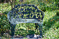 Blue Wrought Iron Bench in a Spring Country Garden. Image taken with a Nikon 1 V1 camera and 30-100 mm VR lens (ISO 100, 30.9 mm, f/5.6, 1/100 sec). .