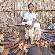 CAPTION: Theresia has many grandchildren, ranging in age from six months to 27 years. She has played an active role in the upbringing of each of them. Before her operation, the really young ones used to find it strange that she looked different to other people and would sometimes ask her where her mouth had gone. LOCATION: Rutare, Byumba-Gichumbi, Rwanda. INDIVIDUAL(S) PHOTOGRAPHED: Theresia Nzabamwita.