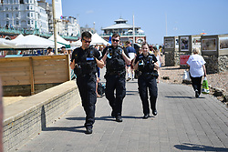 © Licensed to London News Pictures. 22/07/2021. Brighton, UK. Police patrol the beach. As COVID restrictions relax and the UK continues to open up, Brighton experiences an influx of visitors making the most of the summer heat. Meanwhile transmission of the virus continues to double every 9 days. Photo credit: Guilhem Baker/LNP