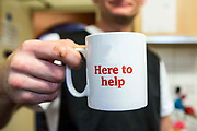 A kitchen volunteer holding up a mug with the slogan 'Here to Help' Slough Homeless our concern (SHOC) A local homeless charity helping the homeless and vulnerable in Slough. Berkshire, UK.