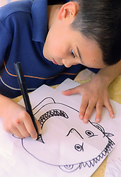 Young boy sitting at table drawing picture of face with felt tip pen,