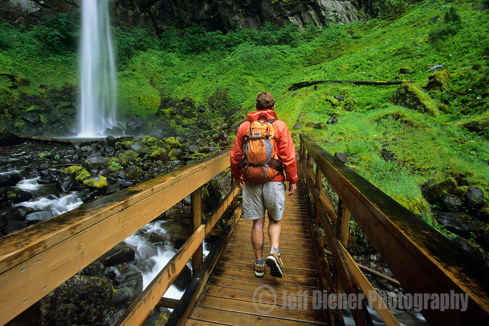 A young man hikes past a waterfall in the Columbia River Gorge, Oregon.