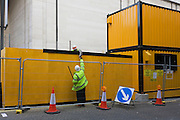A construction site workman passes an item to his colleague by yellow temporary container offices.