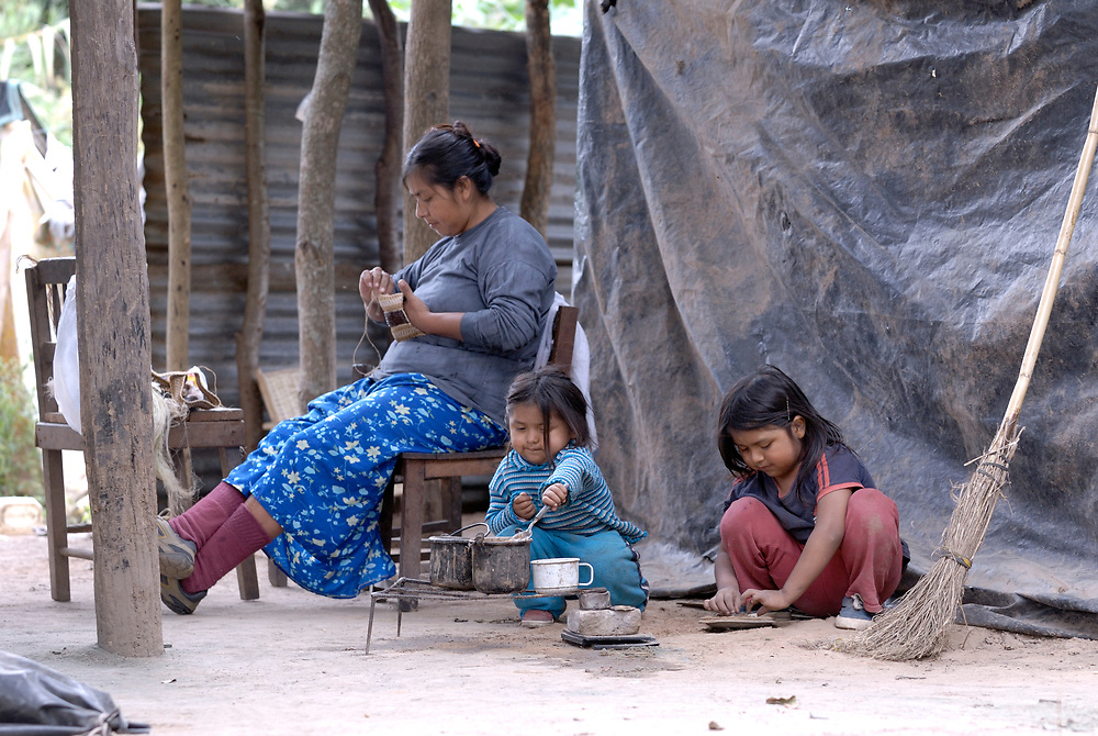 In Lote 75, an indigenous neighborhood of Enmarcacion, in the Chaco region of Argentina, Ibelia Fernandez, 2, plays with Ana Fernandez (right), 4, while their  mother Graciela Sarabia works on artisan crafts that she sells to support the family.