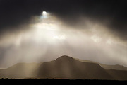 Sunlight streaks through a break in the dark clouds during a rainstorm over the Hengill mountains in southwestern Iceland.