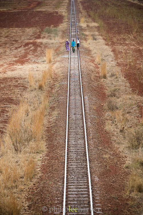 Local people walk along the railway tracks, which stretch from Mombasa on the coast to the capital Nairobi, in Kenya