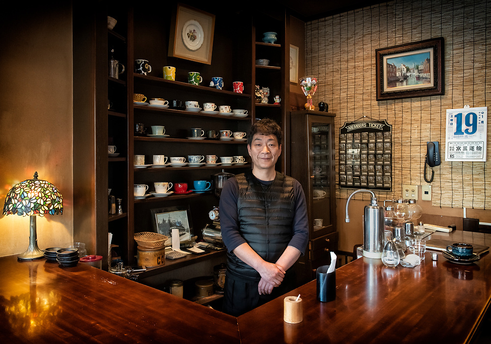 Mr. Takagi Jr. stands for a portrait inside the family cafe Coffee Club in Kyoto, Japan. The delicious coffee is created from an old school syphon orb system, the milk hand whisked with an eclectic and unique selection of cups to choose from.