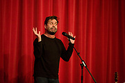 In front of a red curtain, the comedian Phil Nichol performs on stage in London. With the microphone (mic) on its stand, the comic is free to gesture without hindrance, amplifying his voice to the unseen audience, he comic recounts his narrative and gestures to help him make his point. A double shadow is seen on the curtain (drape) from the rudimentary stage lighting. Phil Nichol is a Canadian comedian, singer-songwriter, and actor (source http://www.gloriousmanagement.com/artist/phil-nichol).