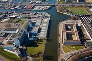 Nederland, Zuid-Holland, Rotterdam, 20-03-2009; Bedrijventerrein Spaanse Polder, met Delfhavensche Schie. Links de voormalige van Nellefabriek voor tabak, koffie en thee. De voormalige fabriek is een Rijksmonument en een voorbeeld van 'Het Nieuwe Bouwen'. Het gebouw van architect Van der Vlugt is nu in gebruik als 'Ontwerpfabriek' en wordt gebruikt voor kantoren, evenementen en dergelijke. Rechts van het van het water Penitentiaire Inrichting 'De Schie' van architect Carel Weeber. Zowel Huis van Bewaring als gevangenis.  Air view on the Business park, with the old Van Nelle factory,  a industrial monument. The building right is prison De Schie ( top)  built by architect Carel Weeber. .Swart collectie, luchtfoto (toeslag); Swart Collection, aerial photo (additional fee required).foto Siebe Swart / photo Siebe Swart