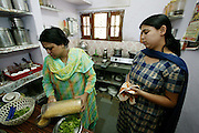 With the aid of her daughter Neha, 19, Sangeeta Patkar prepares a vegetarian breakfast of rice flakes, chickpea-flour noodles and fresh chopped greens in her small, carefully organized kitchen. (Supporting image from the project Hungry Planet: What the World Eats.) The Patkar family of Ujjain, Madhya Pradesh, India, is one of the thirty families featured, with a weeks' worth of food, in the book Hungry Planet: What the World Eats.