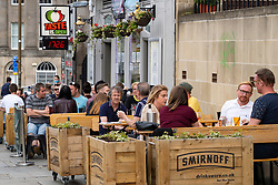 Edinburgh, Scotland, UK. 12 July, 2020, Business slowly returning to normal in Edinburgh city centre. Tourists still almost non existent and streets remain very quiet in the Old Town. People sitting outside Planet Bar and kitchen.Iain Masterton/Alamy Live News