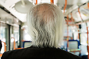 senior man with greying and white hair seen from behind