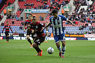 Queens Park Rangers Danny Simpson and Wigan Athletic's Jordi Gomez battle for the ball. Skybet football league championship play off semi final, 1st leg match, Wigan Athletic v QPR at the DW Stadium in Wigan, England on Friday 9th May 2014.<br /> pic by Chris Stading, Andrew Orchard sports photography.