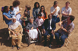 Multiracial group of people including woman with disability; who is wheelchair user; people with hearing impairments using sign language to communicate and man with Downs Syndrome,