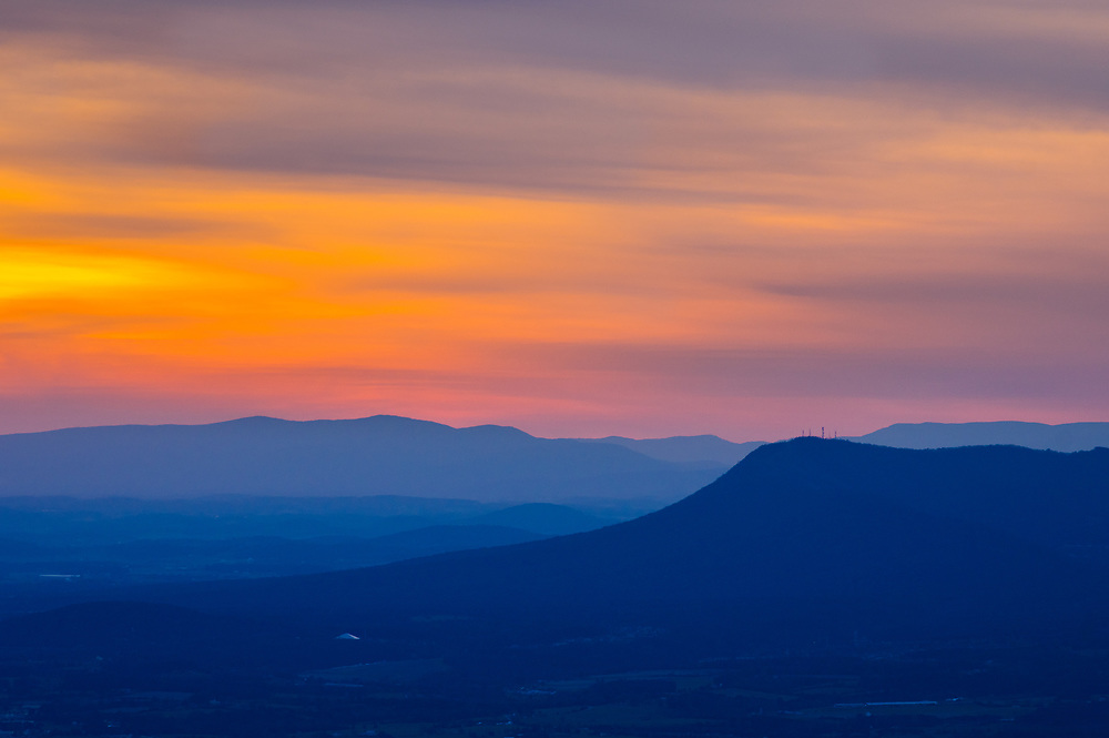 Virginia's Shenandoah Valley rests in the distant blue haze marked by the increasingly lighter ridgelines with Massanutten mountain rising sharply above them all, under a dramatic fiery late evening sky shifting between the blues and yellow hues.