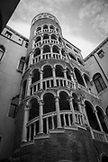 "Black and white photo of The Palazzo Contarini del Bovolo, best known for its external multi- arch spiral staircase known as the Scala Contarini del Bovolo (literally, ""of the snail"")."