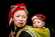 Vietnam, Sapa. Young Red Dzao woman carrying her little baby on her back.