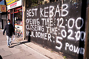 The handwritten capital letters proclaiming the best kebabs and the businesss opening times on the Commercial Road in the East End, on 21st October 2021, in London, England.