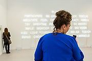 """New York, NY - 5 May 2017. The opening day of the Frieze Art Fair, showcasing modern and contemporary art presented by galleries from around the world, on Randall's Island in New York City. A woman checks her phone in front of an installation of neon tubes by Jeppe Hein, """"Please Participate,"""" in the 303 Gallery."""