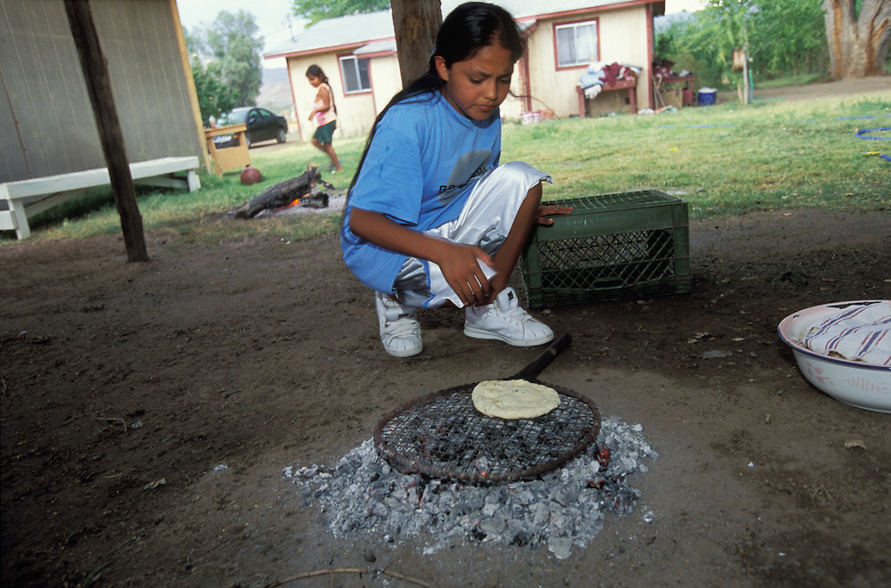 An Apache girl learns how to make corn bread as part of the preparation for her Sunrise Dance, a first menstruation rite, on the San Carlos Apache Indian Reservation in Arizona, USA. June 2004. The Sunrise Dance is the most important ceremony of the Apache Indians. It is held during the summer, within one year after the girl has had her first menstruation, and lasts for four days. The ceremony is an enactment of the Apache creation myth and during the rites the girl 'becomes' Changing Woman, a mythical female figure, and comes into possession of her healing powers. The rites are also supposed to prepare the girl for adulthood and to give her a long and healthy life without material wants.