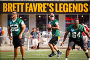 Former Green Bay Packers quarterback Brett Favre (4) looks to pass as former Packers Frank Winters, (52) and Bruce Wilkerson hold the line during during  a chairity flag football game. Favre was inducted into the Packers Hall Fame the following day. (AP Photo/Andy Manis)