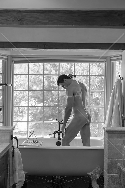 naked bodybuilder showering off in a sexy bathtub