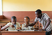 Elias Delgado, 17 and Cledia Ferreira Ramos, 17, are given English lessons by teacher Arsenio Dos Ramos at the Principe High School, Principe, Sao Tome and Principe<br /> Sao Tome and Principe, are two islands of volcanic origin lying off the coast of Africa. Settled by Portuguese convicts in the late 1400s and a centre for slaving, their independence movement culminated in a peaceful transition to self government from Portugal in 1975.