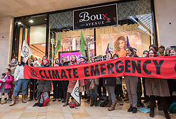 "© Licensed to London News Pictures. 15/12/2018. Bristol, UK. 'Extinction Rebellion' campaign event ""Bristol Rebellion Day"" to draw attention to the catastrophic impact of the fast-fashion industry and Christmas on our climate and ecological systems, part of a national day of action in many towns and cities about the threat of climate change. Regional Extinction Rebellion groups are taking part non-violent action to put pressure on local councils to transform policy in line with national demands to act on climate change. Campaigners say Bristol City Council is leading the way, having declared a climate emergency in November. Campaigners gathered inside Cabot Circus on the bottom floor, with songs from the XR Choir and a die in where all activists will lay on the floor. The campaign wants to make ecocide a crime in UK law, saying the threat of climate change threatens the lives of millions of people on the planet. The campaign is organised by Rising Up. Photo credit: Simon Chapman/LNP"