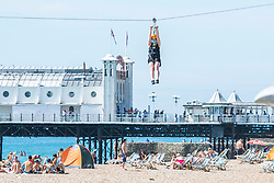 © Licensed to London News Pictures. 06/08/2020. Brighton, UK. Members of the public take a ride on the Brighton Zip Line attraction in Brighton And Hove as sunny and hot weather is hitting the seaside resort. Photo credit: Hugo Michiels/LNP