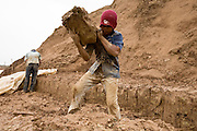30 JUNE 2006 - PHNOM PENH, CAMBODIA: Brick factory workers stack mud which will be turned into brick at a brick factory in Phnom Penh, Cambodia. According the United Nations Food and Agricultural Organization, there are more than 70 brick factories in Phnom Penh and its environs. Environmentalists are concerned that the factories, most of which burn wood in their kilns, contribute to deforestation in Cambodia. They are encouraging factory owners to switch to burning rice husks, as brick kilns in neighboring Vietnam do. The brick factories are kept busy feeding Phnom Penh's nearly insatiable appetite for building materials as the city is in the midst of a building boom brought by on economic development and the need for new office complexes and tourist hotels.   Photo by Jack Kurtz / ZUMA Press